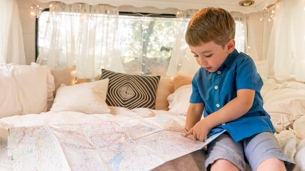 キャラバンに座っていると地図を見る少年 無料写真
