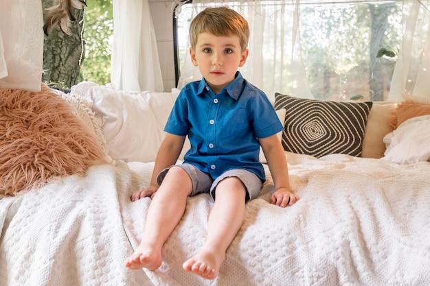 Маленький мальчик сидит в своем караване плохо Бесплатные Фотографии