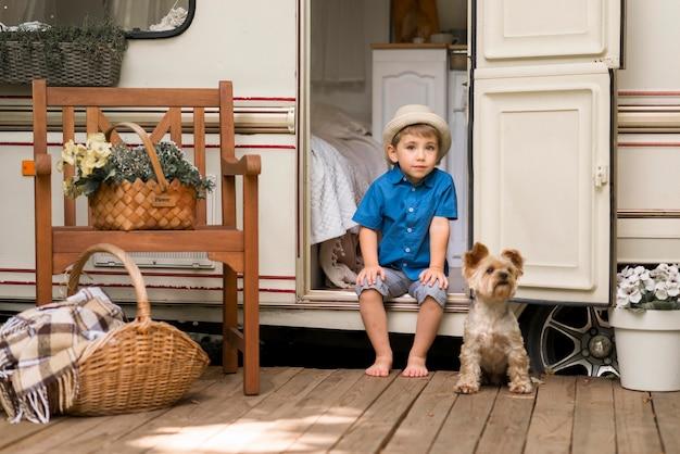 かわいい犬の横にあるキャラバンに座っている少年 無料写真