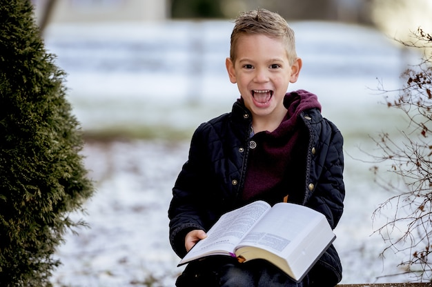 木の板の上に座って、雪に覆われた庭で聖書を読む少年 無料写真