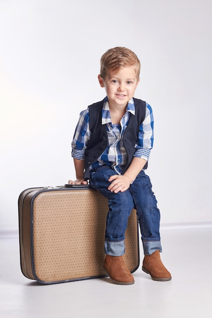 Little boy sitting on suitcases, preparing holiday Premium Photo