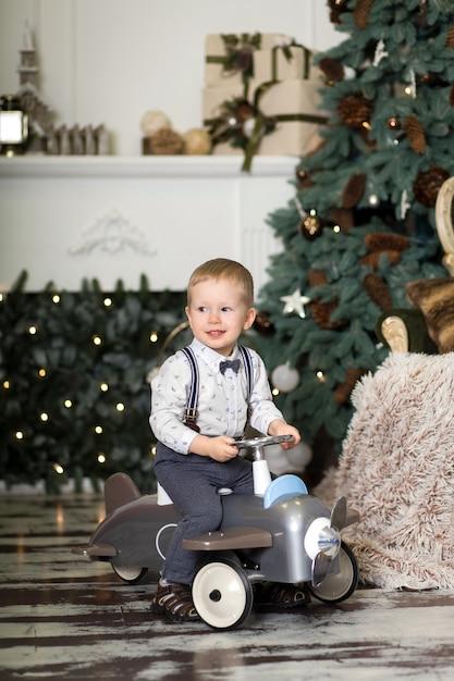 Little boy sitting on a vintage toy airplane near a christmas tree. Premium Photo
