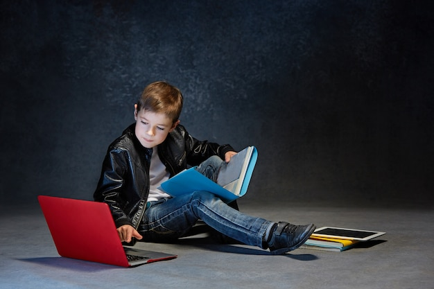 Little boy sitting with gadgets Free Photo