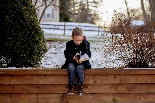 Ragazzino seduto su assi di legno e leggere la bibbia in un giardino coperto di neve Foto Gratuite
