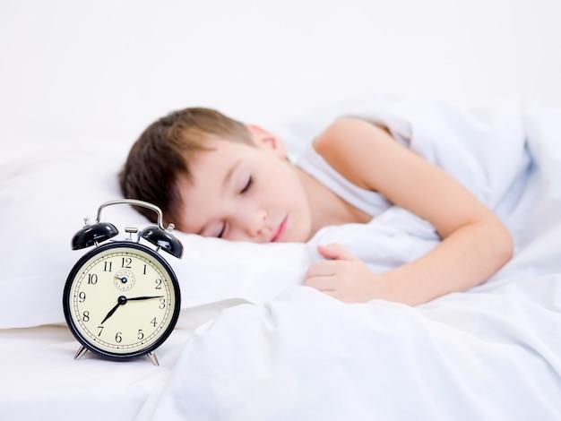 Маленький мальчик спит с будильником возле его головы Бесплатные Фотографии