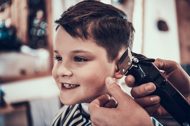 The little boy smiles when his hair is cut. Premium Photo
