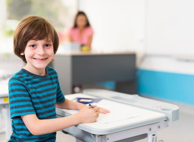 Маленький мальчик улыбается, сидя за своим столом Бесплатные Фотографии