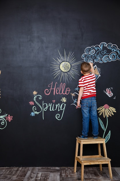 Little boy standing and drawing easter doodles Free Photo