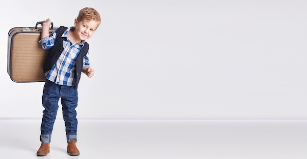 Little boy standing suitcase in hand, vacation Premium Photo