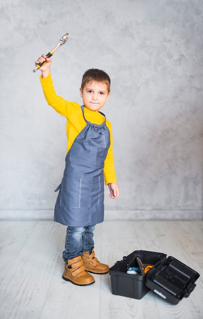 Little boy standing with spanner Free Photo