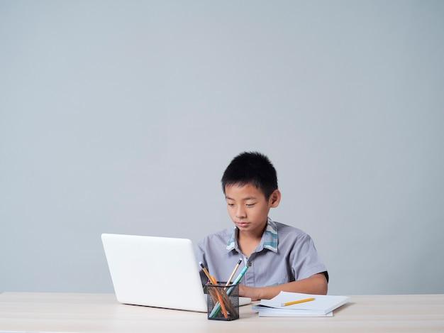Маленький мальчик учится онлайн с ноутбуком. дистанционное обучение во время пандемии covid-19 Premium Фотографии