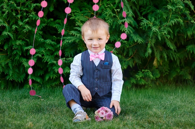 Little boy in a suit with a bouquet sitting on the grass Premium Photo