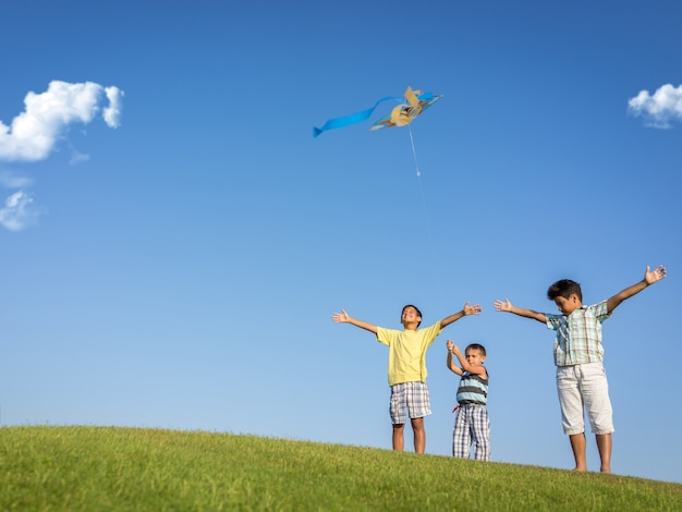 Little boy on summer vacation having fun and happy time flying kite on the sea beach Premium Photo