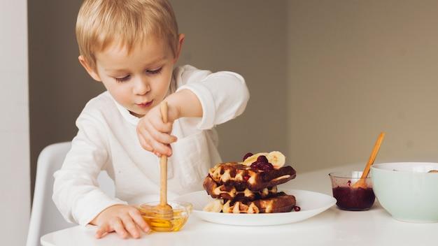 Little boy taking honey Free Photo