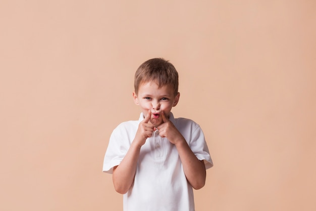 Little boy teasing and looking at camera standing near beige background Free Photo