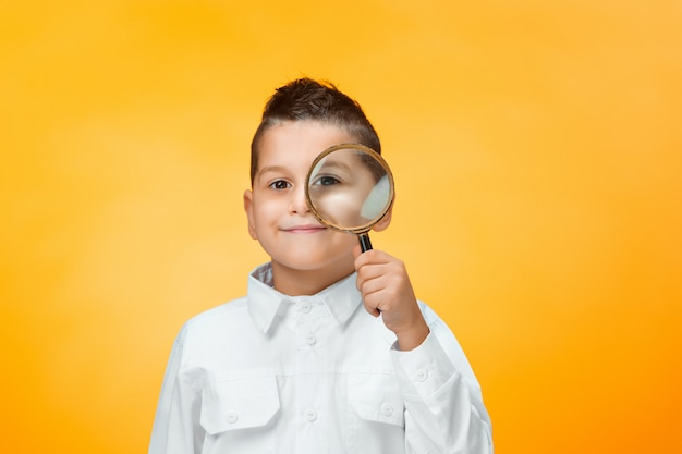 Little boy using magnifier looking close up Free Photo