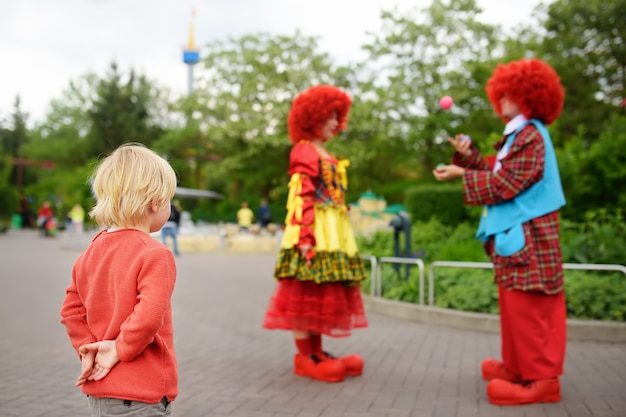 Little boy watches performance funny clowns in legoland deutschland at sunny day. Premium Photo