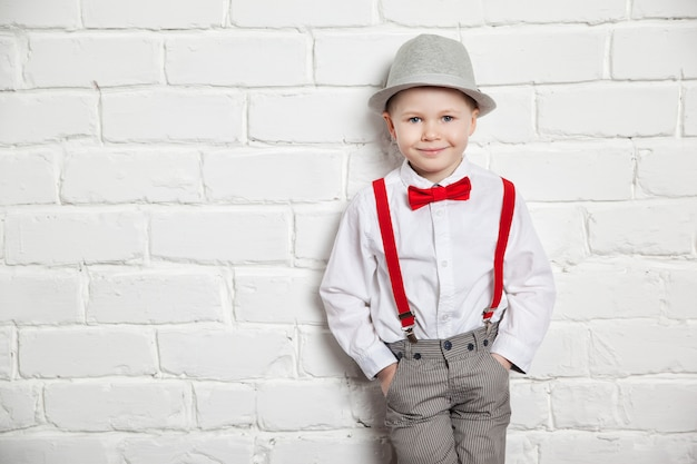 Little boy wearing a red bow tie, suspenders and white shirtand against a white brick wall Premium Photo