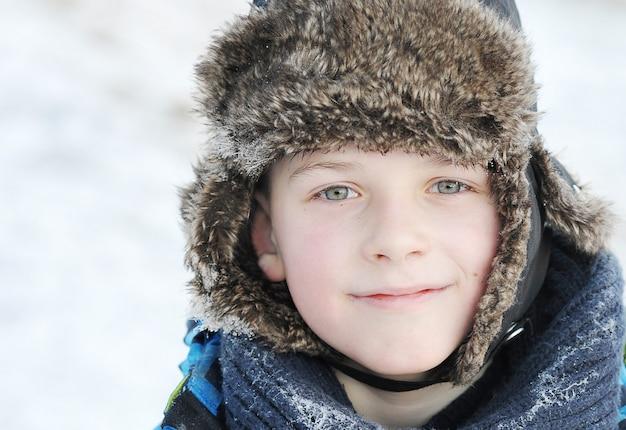 Little boy in winter a fur hat in winter Premium Photo