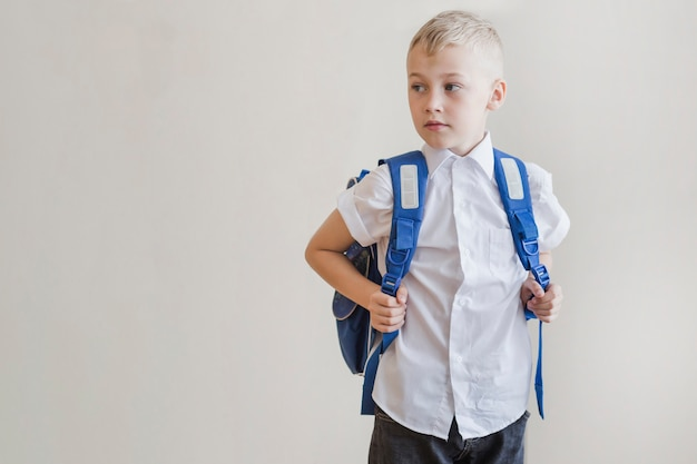 Little boy with backpack in studio Free Photo