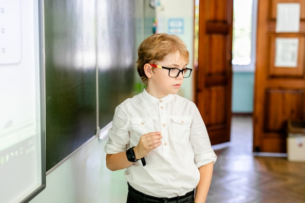 Little boy with big black glasses and white shirt standing near school blackboard with a piece of chalk making smart thinking face Premium Photo