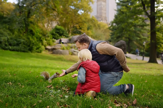Little boy with his father feeding squirrel in central park, manhattan, new york. Premium Photo