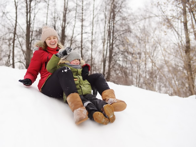 Little boy with his mother enjoy riding on ice slide in winter Premium Photo