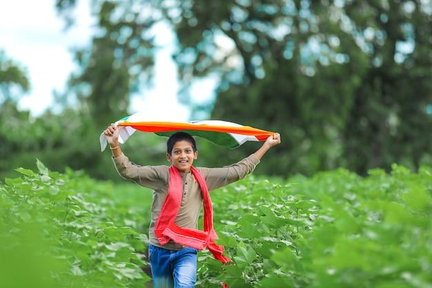 自然の中でインドの旗を持った少年 Premium写真