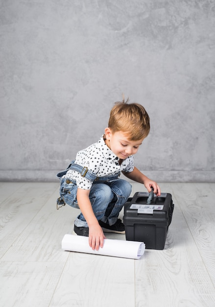 Little boy with tool box and paper roll Free Photo