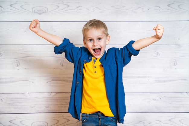 Little boy in yellow t-shirt and blue shirt showing happiness with opened mouth. smiling child with spreading his hands Premium Photo