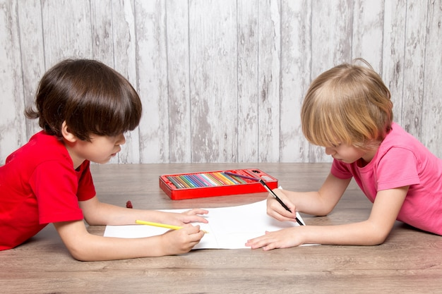 Little boys in pink and red t-shirts drawing Free Photo