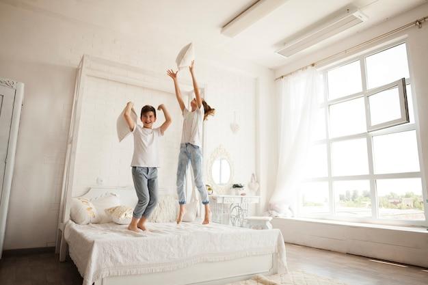 Маленький брат и сестра весело прыгать на кровати в спальне Бесплатные Фотографии
