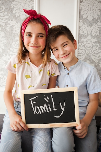 Little brother and sister holding slate with family text looking at camera Free Photo