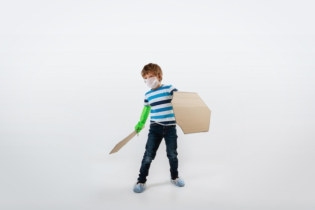Little caucasian boy as a warrior in fight with coronavirus pandemic, with a shield, a spear and a toilet paper bandoleer, attacking Free Photo