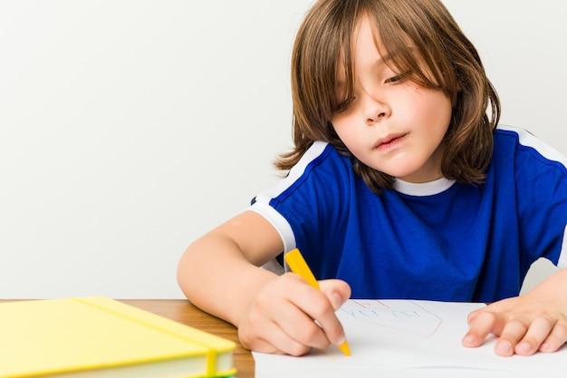 Little caucasian boy drawing Premium Photo