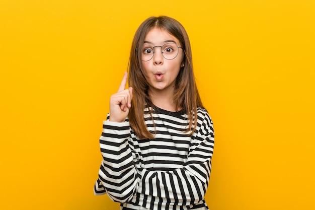 Маленькая кавказская милая девушка имея некоторую отличную идею, концепцию творческих способностей. Premium Фотографии