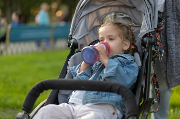 Little caucasian girl dressed in a denim jacket drinks juice from her bottle while sitting in a baby carriage Premium Photo