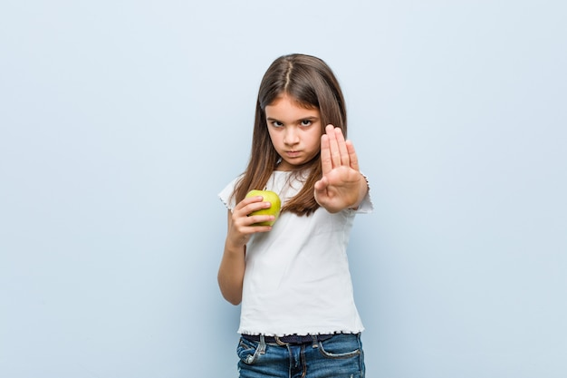 Little caucasian girl holding a green apple standing with outstretched hand showing stop sign, preventing you. Premium Photo