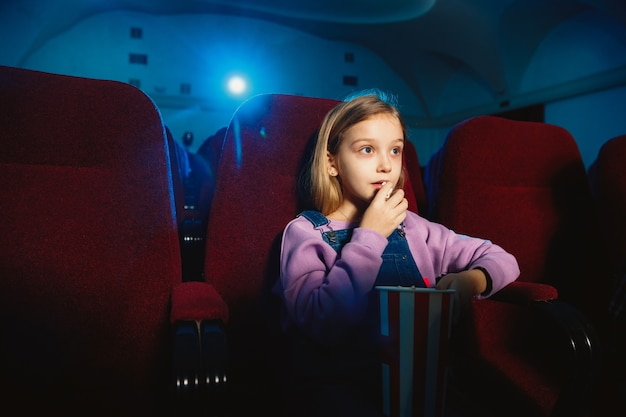 Little caucasian girl watching a film at a movie theater, house or cinema. Free Photo