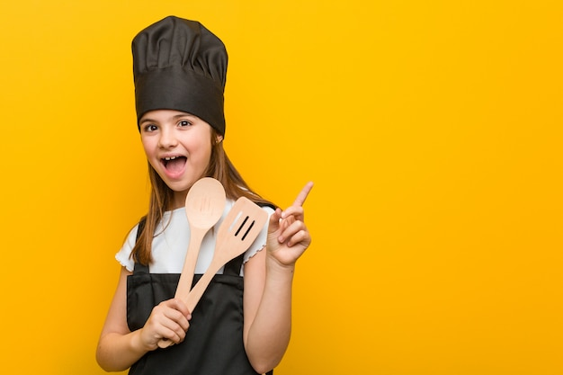 Little caucasian girl wearing a chef costume smiling cheerfully pointing with forefinger away. Premium Photo