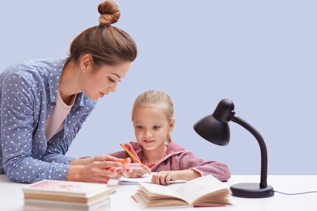 작은 매력적인 여자 테이블에 앉아 어려운 숙제 작업, 딸을 돕고 수학 규칙을 설명하려고하는 어머니, 좋은 비전을위한 독서 램프를 사용하려고합니다. 교육 개념. 무료 사진