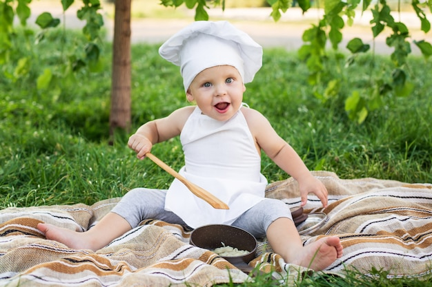 Little chef cooks and eats pasta on a picnic outdoors Premium Photo