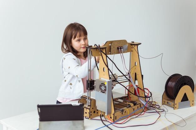 3dプリンターを使用して小さな子供の建築家。女子高生、技術、研究コンセプト。 Premium写真