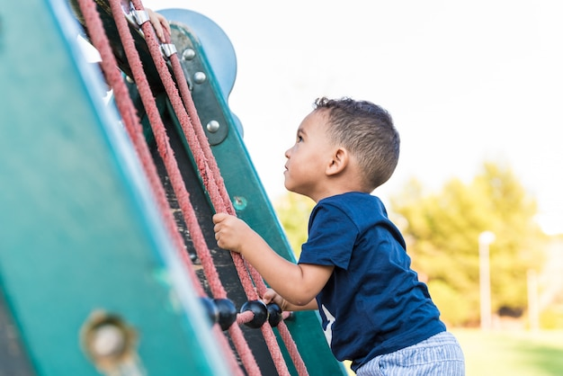 Little child boy climbing a rope in the park. Premium Photo