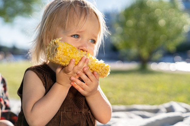 Little child girl eat sweet corn cob, sitting on plaid on grass in summer day. healthy eating. Premium Photo