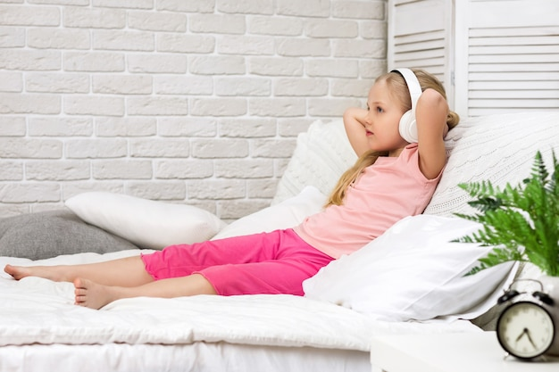 Little child girl listening to the music with the headphones Premium Photo