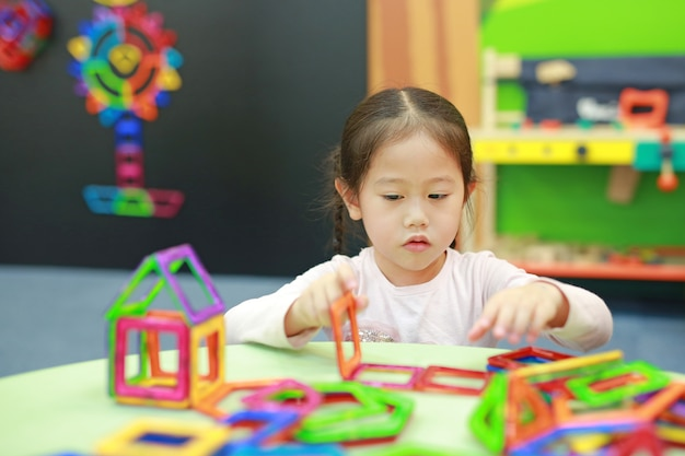 Little child girl playing magnets toy for brain development. Premium Photo
