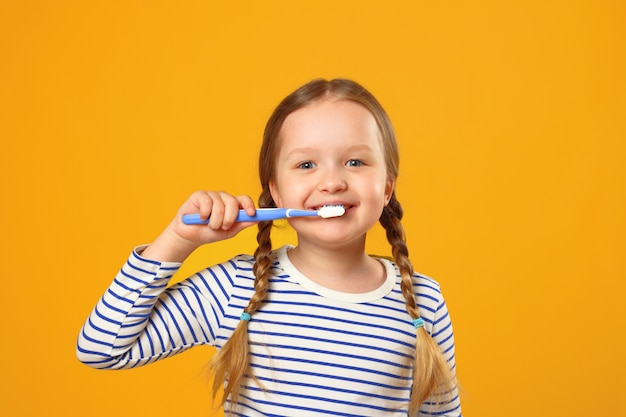 Little child girl in striped pajamas brushing her teeth with a toothbrush Premium Photo