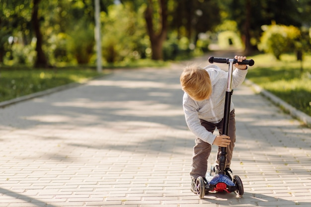Little child learning to ride a scooter outdoors Free Photo