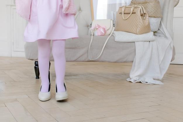 Маленький ребенок, играющий с мамой на высоких каблуках Premium Фотографии